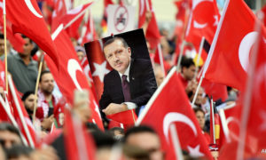A picture of Turkish president Erdogan is framed  by national flags during a demonstration in Cologne, Germany, Sunday, July 31, 2016. Thousands of supporters of Turkish President Recep Tayyip Erdogan have gathered in the German city of Cologne for a demonstration against the failed July 15 coup in Turkey.  (AP Photo/Martin Meissner)