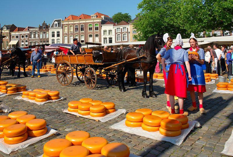 Käsemarkt mit Frauen in holländischer Tracht und Pferdewagen, Gouda, Südholland, Niederlande
